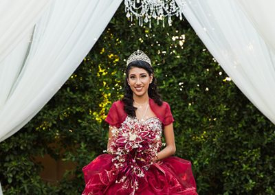 quinceanera in red dress posing for pictures in garden