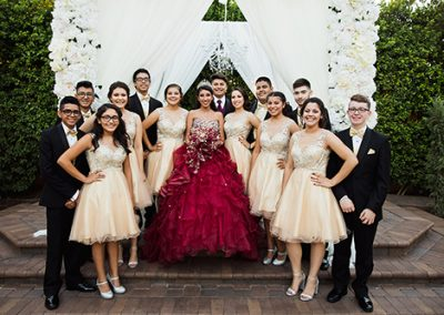 Quinceanera posing outside with guests