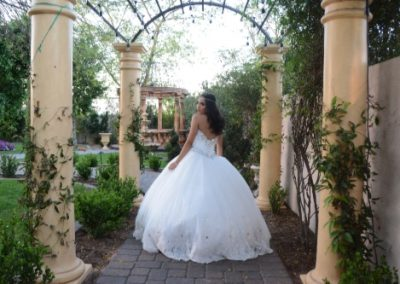 Quinceanera showing off white gown in outdoor Garden