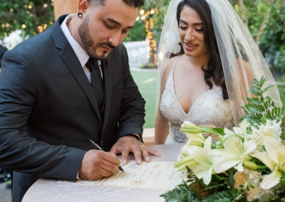 Garden Tuscana Reception Hall event in Mesa showing newlywed couple signing marriage license
