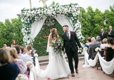 Garden Tuscana Reception Hall event in Mesa showing bride and groom walking down aisle